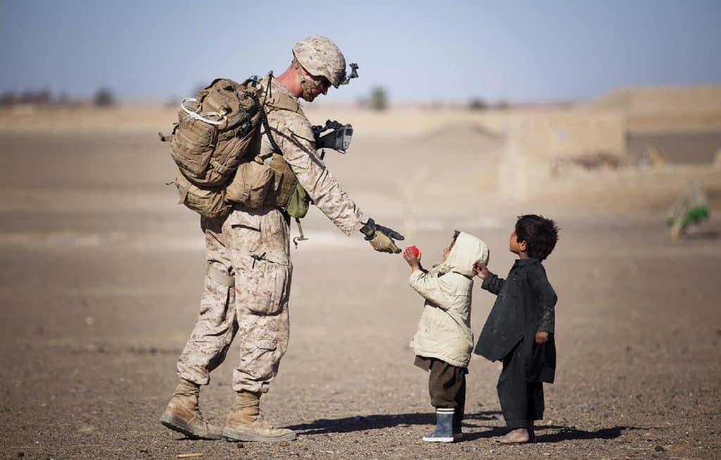 Soldat militaire tend la main à deux enfants